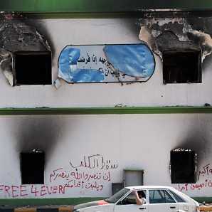 A car drives by a bulding of Katiba from where Gaddafi army shot dead several protesters.