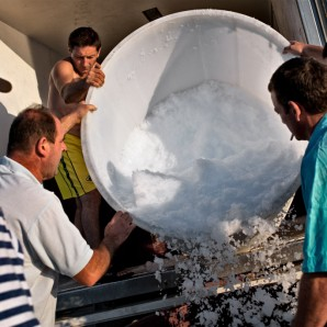 The crew carries ice on board of the Komarča to keep fish fresh.