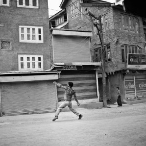 A young Kashmiri throw stones towards the police during a protest.
