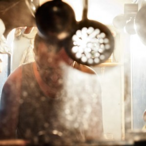 A member of the crew washes dishes.