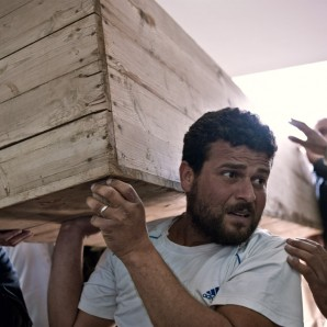 A man carries an empty coffin inside the morgue in Benghazi.