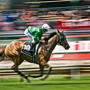 A jockey spurs his horse towards the finish line.