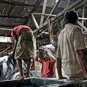Workers handle processed leather without any protections.