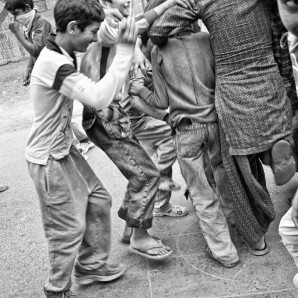 Kids stomping on the Indian flag drawn on the street.