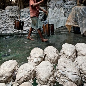 A worker carries liquid waste to be reused in a small tannery.