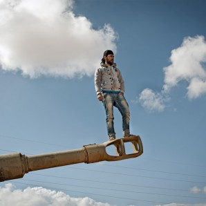 A man stands on top of a tank gun after the UN airstrike destroyed most of the Gaddafi armored vehicles outside Benghazi.