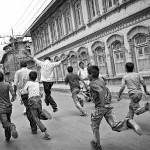Youngsters pretending to run towards the police during a protest.